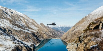 helicopter flys between mountains and lake | © Marko Roth